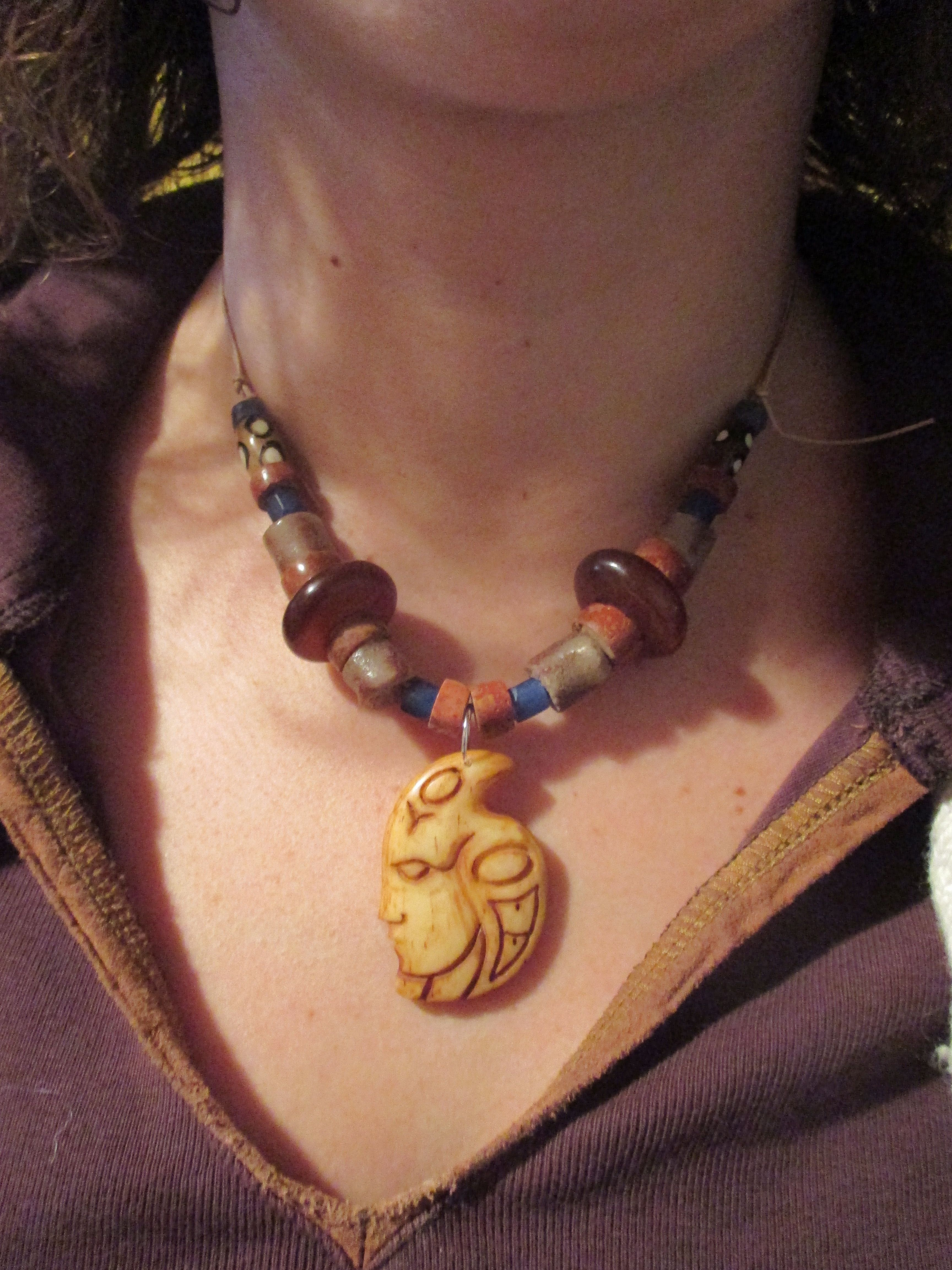 Carved bone charm on leather cord with trade beads